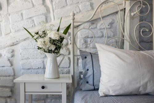Habitación nº 4 detalle de la cama y pared de adobe, madera y piedra blanca