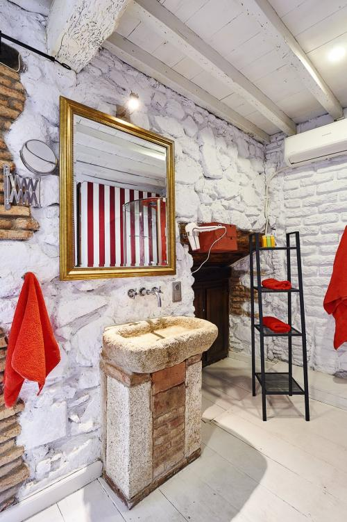Bonita foto del diseño del cuarto de baño de la casa rural en la Vera (Cáceres). Habitación Juglar o nº1 de Casa rural La Posada de los Sentidos, un estilo arquitectónico muy cuidado y con mucho encanto el interiorismo, podrás crear nuevos recuerdos inolvidables con tu pareja en la Posada. Únicos y maravillosos. Foto del lavabo en piedra de época romana, hacen especial a esta bonita habitación en una casa con encanto. Cuidamos los detalles, el interiorismo y arquitectura. Queremos recuperar y mantener nuestro patrimonio.